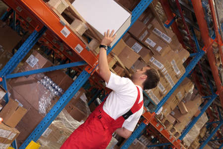 storeroom: A worker in a factory keeping packages of finished products on the shelves in a storeroom.