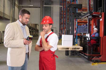 storeroom: boss talking to worker in uniform in factory