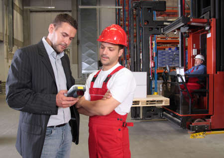 construction manager: boss talking to worker in uniform in factory