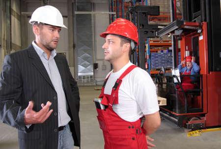 foreman: boss talking to worker in uniform in factory