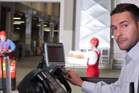 dinamismo: maschio operatore premendo i tasti del pannello di controllo in magazzino