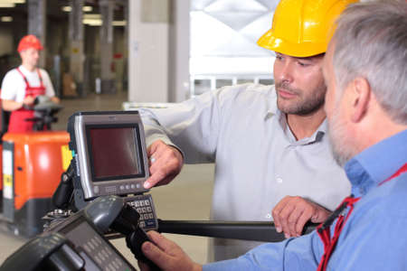 inspection: supervisor talking to engineer operator in warehouse Stock Photo