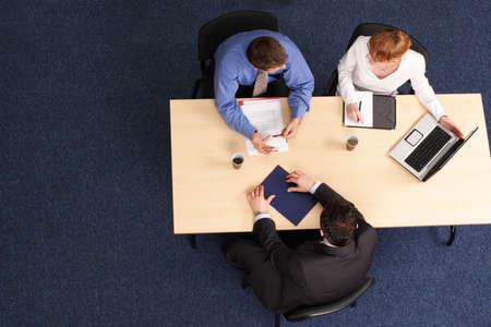 Empresarios se reunieron alrededor de una mesa para una reunión, takling sobre la estrategia.