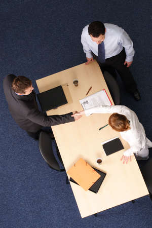 mediation: female business employee shaking the hand of an new male employee, while male employee, interest, look on. In an office setting. Stock Photo