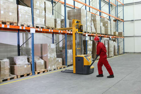 packaging industry:  forklift operator at work in warehouse Stock Photo