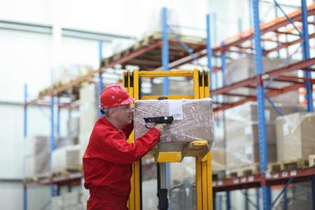 warehouse interior: lavoratore con lettore di codice a barre in magazzino