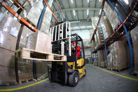 carretillas almacen: operador del cami�n montacargas en el trabajo en almac�n