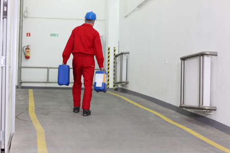 Back view of a factory worker carrying bottles of chemicals photo