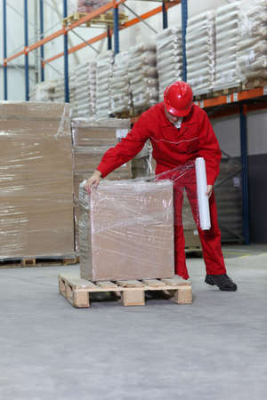 plastic wrap: worker wrapping box on wooden pallet in warehouse Stock Photo