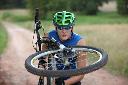 Biker looking at spokes in  wheel of his bike Stock Photo - 7716988