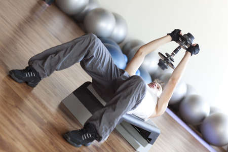 dumbell: A man lifting weights and exercising.