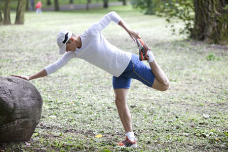 runner up: young man   stretching before running in a park