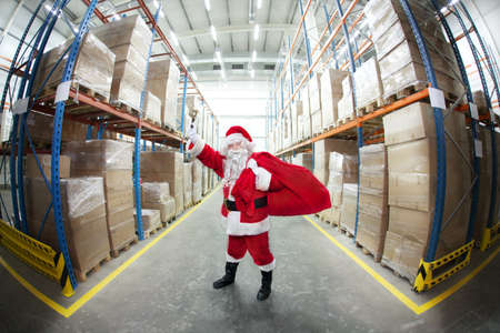 commercialism: Santa Claus with sack of gifts, ringing in a bell in storehouse full of gifts Stock Photo