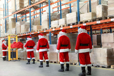 team of santa clauses standing in the line for the sacks of gifts in storehouse photo