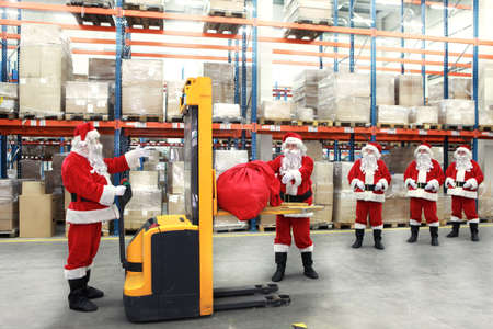 group of santa clauses standing in the line for the sacks of gifts in storehouse photo