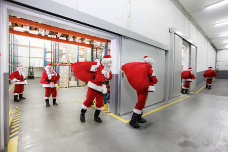 irony: group of santa clauses leaving a gift distribution center with red sacks