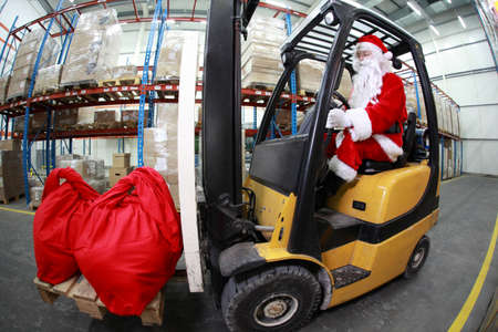 shipping supplies: Santa Claus as a forklift operator at work in warehouse. 2 large red sack at the front of forklift.fish-eye lens