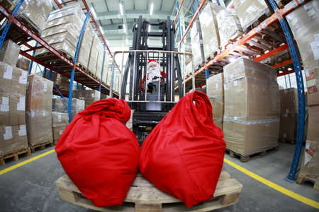 Santa Claus as a forklift operator at work in warehouse. 2 large red sack at the front of forklift.fish-eye lens photo