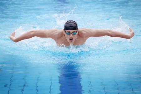 respiration: Nageur en bonnet et lunettes de respirer effectuant la nage papillon Banque d'images