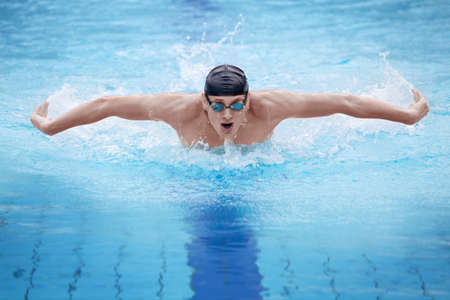 Swimmer in cap and goggles breathing performing the butterfly stroke photo