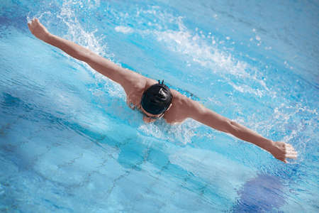 water aerobics: Swimmer in cap performing the butterfly stroke