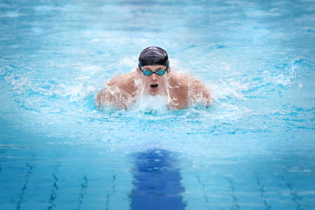 Swimmer in cap breathing performing the butterfly stroke  photo
