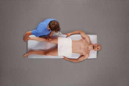 masseur: Muscular man being massaged by therapist  Stock Photo