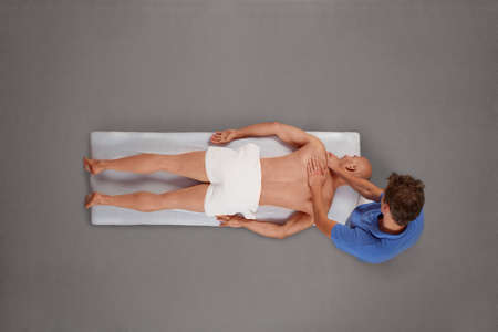 Overhead view of male therapist massaging muscular man back and neck