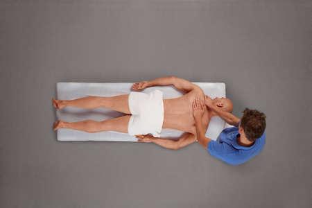 shiatsu: Overhead view of male therapist massaging muscular man back and neck