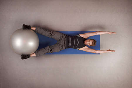 overhead view: Overhead view of man exercising with large ball