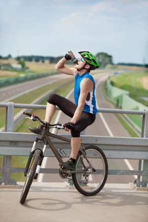 isotonic: Mountain biker drinking isotonic drink and having rest over highway