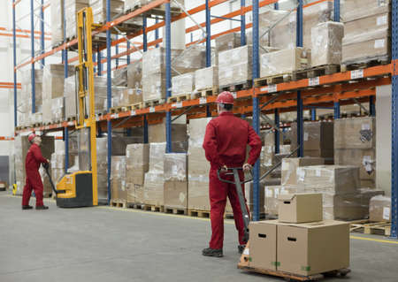 supplychain: Two workers in uniforms and safety helmets working in storehouse  Stock Photo