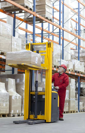 warehouse cargo: Senior worker manual forklift operator in red uniform at work in warehouse