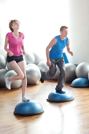 Couple working out by running in place on pilates balls. photo