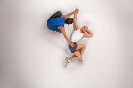 athletic man stretching with personal trainer  photo