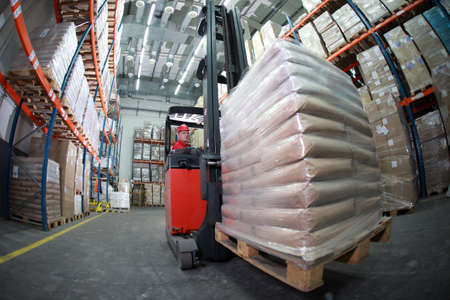 warehouse equipment: Forklift operator in red uniform and blue helmet at work in warehouse