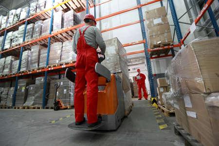 carretillas almacen: Entrega de bienes - dos trabajadores en almacén con cargador de carretilla  Foto de archivo