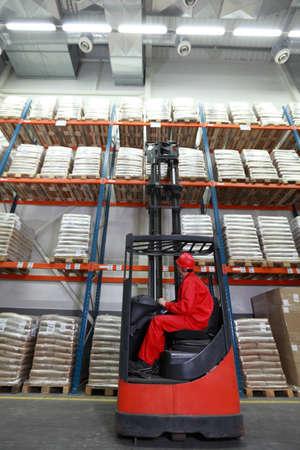 carretillas almacen: De los trabajadores en uniforme rojo y sacos de seguridad de los cascos de carga con cargador de carretilla elevadora en el almacén