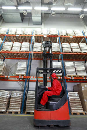 Worker in red uniform and safety helmet loading sacks with forklift loader in warehouse  photo