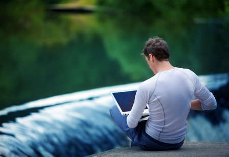Man with notebook sitting at the bank of river over the waterfall  photo