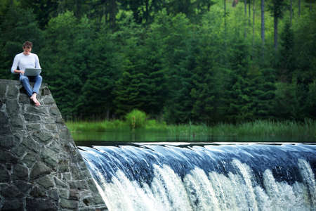 blogosphere: Man with notebook sitting at the bank of river over the waterfall Stock Photo