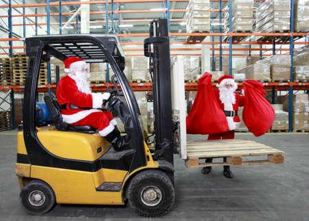 Due Babbi Natale che lavorano in magazzino moderno con i regali Archivio Fotografico