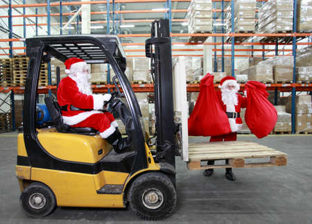 Two Santa clauses working in modern storehouse with gifts photo