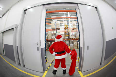 commercialization: Santa Claus with empty sack doing wholesale shopping. At the gate to Gifts Distribution Center