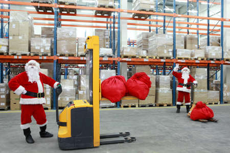 three shelves: two santa clauses workers at work in large storehouse