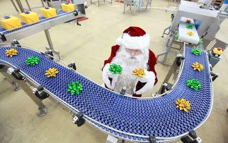 conveyor: santa claus at christmas ornament production line in factory