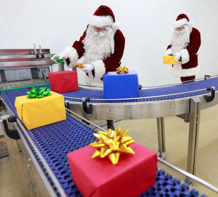 commercialization: Two santa clauses working at production line Stock Photo