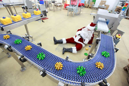 tired overworked santa claus in factory photo
