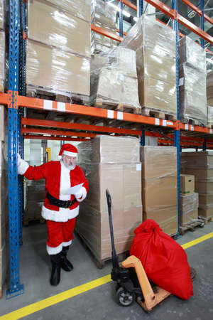 commercialization: Santa claus checking wishing list of presents in storehouse Stock Photo