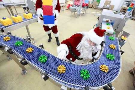 cinta transportadora: Santa Claus en la línea de producción de adornos de Navidad en la fábrica de